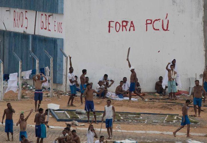 Presos de la cárcel de Alcacuz, cerca de Natal, Brasil, continúan atrincherados con machetes, el viernes 20 de enero de 2017. (AP/Felipe Dana)