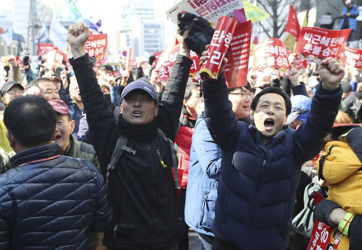 Los manifestantes festejan el veredicto de la Corte Constitucional durante una protesta donde pedían la destitución de la presidenta Park Geun-hye. (AP/Lee Jin-hombre)