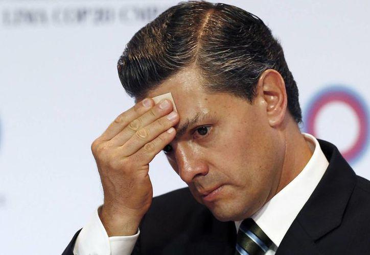 El presidente mexicano Enrique Peña Nieto se limpia el sudor de la frente durante la firma de documentos entre la Alianza del Pacífico en la Conferencia sobre Cambio Climático en Lima, Perú. (Foto: Archivo Agencias)