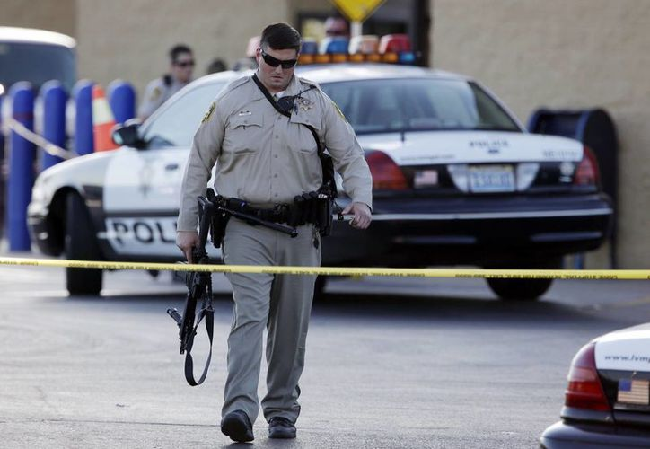 Foto de archivo del domingo 8 de junio de 2014, un policía de Las Vegas se aleja del lugar de una balacera cerca de una tienda Wal-Mart, en Las Vegas. (Foto AP/John Locher, archivo)