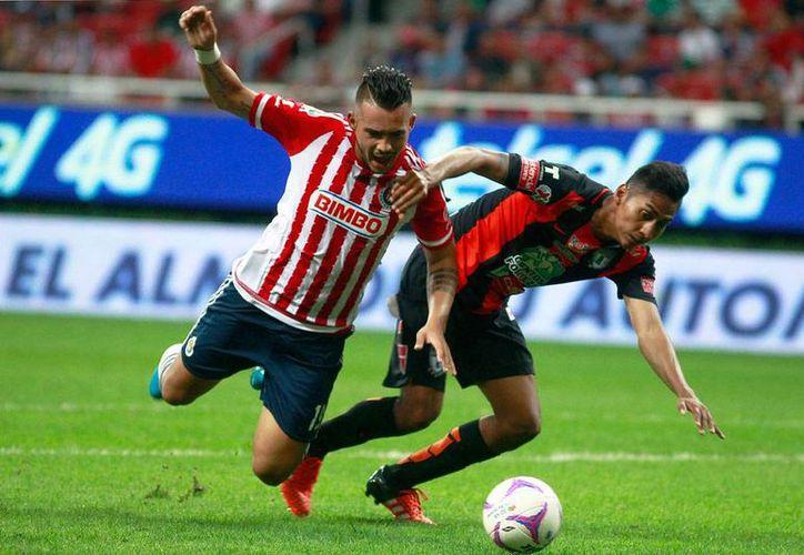 Michel Vázquez (izq) cae luego de chocar contra Hugo Rodríguez, acción que el árbitro consideró falta en el área. Omar Bravo aprovechó el 'regalito' del árbitro  empató el partido frente a Tuzos. (Jammedia)