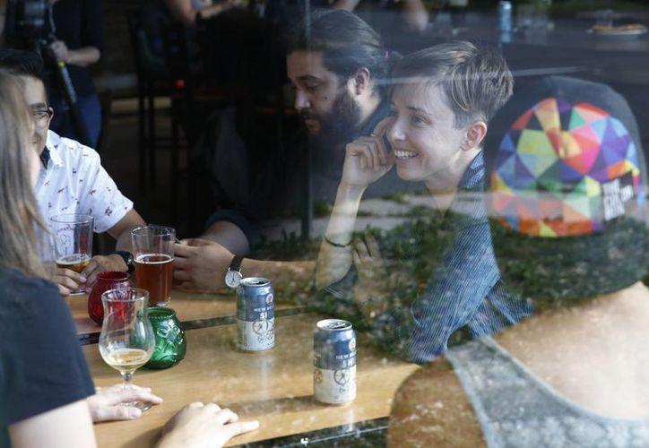 Diana Downard, de 26 años y seguidora de Bernie Sanders que dice que votará a Hillary Clinton, toma unos tragos con amigos en un pub en Denver. 'Los millennials han sido descritos como apáticos, pero no lo son', dijo Downard. (AP/Brennan Linsley)
