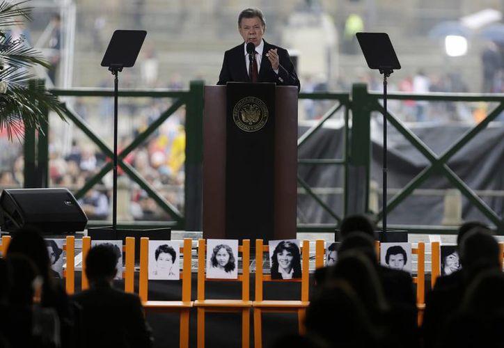 Este jueves, durante un acto conmemorativo, el mandatario colombiano, Juan Manuel Santos, pidió perdón a los familiares de las víctimas de la matanza del Palacio Judicial y llamó a los ciudadanos a buscar la paz en pro del país. (AP)