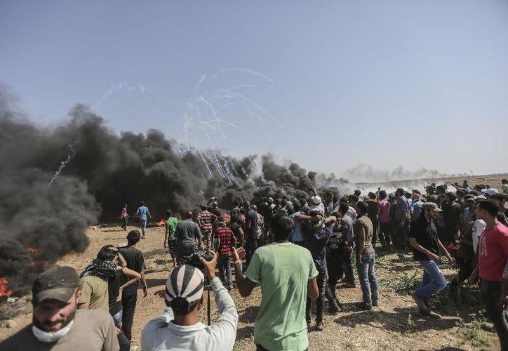 Manifestantes palestinos corren para cubrirse del gas lacrimógeno lanzado por soldados israelíes durante enfrentamientos en la frontera entre Gaza e Israel, el 8 de junio de 2018. (Foto: La Jornada)