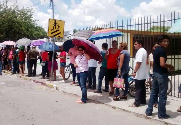Imagen de la larga fila que se formó en las puertas de una escuela de la costa de Yucatán, en donde se instaló una de las casillas en esta jornada electoral.(Jesús Erosa/SIPSE)