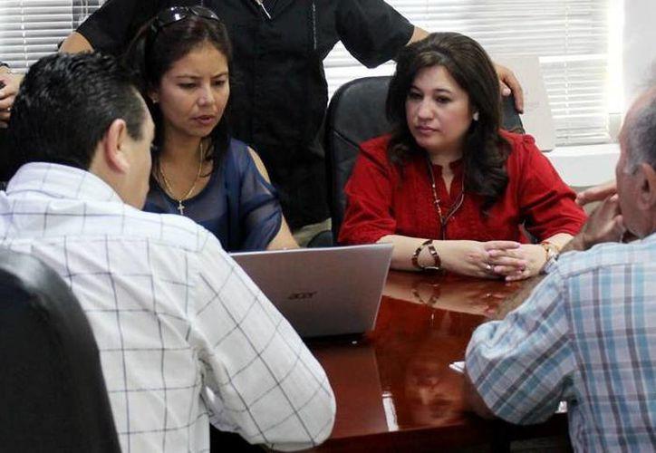 La fiscal estatal, Celia María Rivas Rodríguez, escucha a Dania de los Santos, gerente general sureste de la OCRA. (Milenio Novedades)