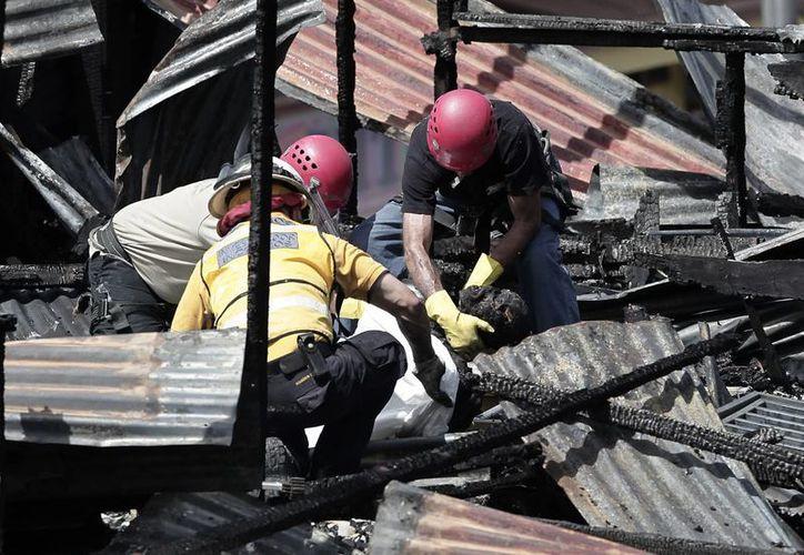 Autoridades realizan labores de búsqueda y rescate como consecuencia del incendio que consumió el pequeño motel. (EFE)