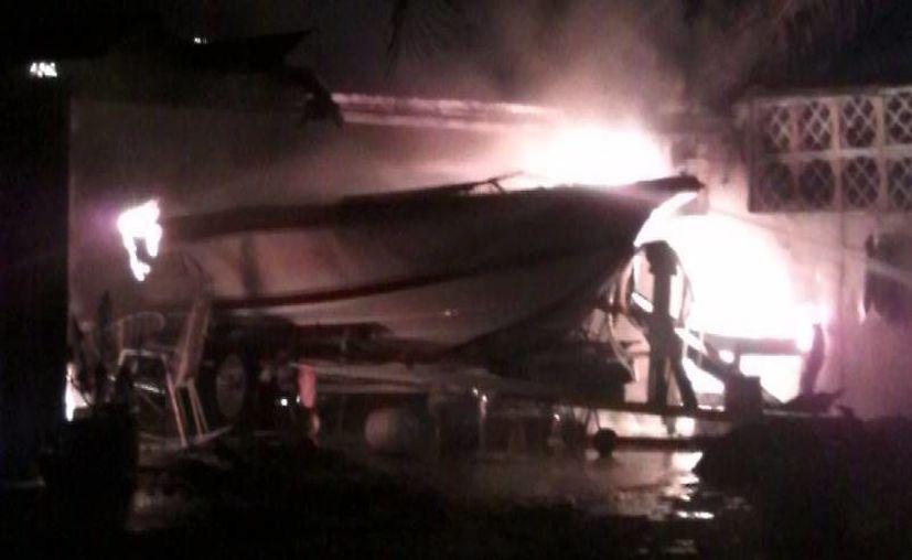 Una lancha que se encontraba en una casa de Progreso se quemó con todo y motor. (Gerardo Keb/SIPSE)