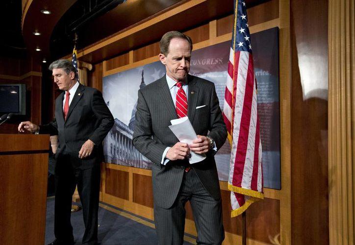 Los senadores Pat Toomey, republicano de Pensilvania, a la derecha, y Joe Manchin, demócrata de Virginia Occidental, terminan una conferencia de prensa en el Capitolio en Washington. (Agencias)