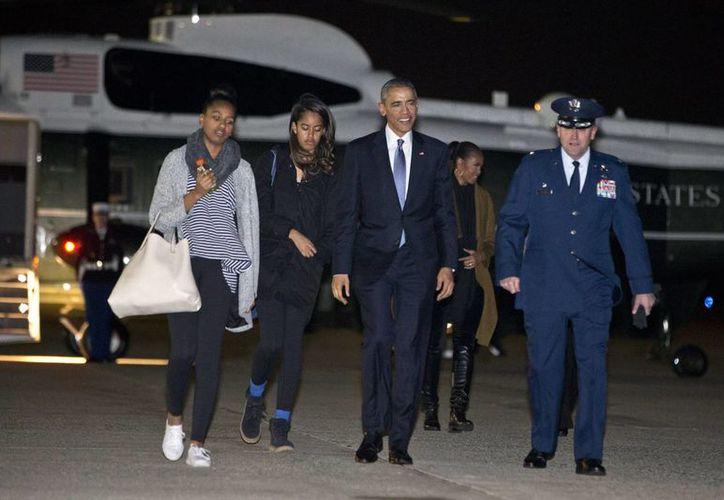 "La primera familia, Sasha (izq), Malia, el presidente Obama y la primera dama Michelle Obama, en segunda fila, al descender del helicóptero presidencial ""Marine One"". (Agencias)"