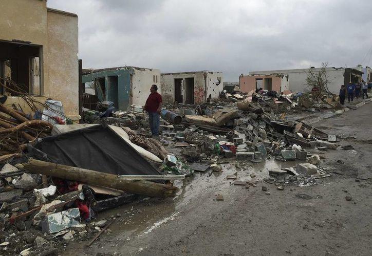 Un hombre busca entre los escombros de casas dañadas algunas pertenencias, luego del paso de un poderoso tornado que barrió y destruyó Ciudad Acuña, Coahuila. Aumentó el número de muertos a 14. ( AP Photo )