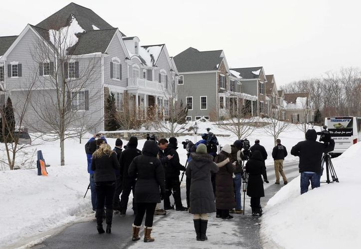 Representantes de medios de comunicación y oficiales de policía, junto a una parada de autobús situada frente a la casa del exjugador de Patriotas de la NFL, Aaron Hernández, como parte del juicio para resolver el asesinato de Odin Lloyd. (Foto: AP)