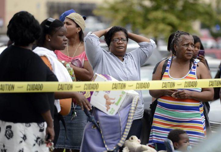 Detalle de padres preocupados mientras policías y personal de emergencias evacuaban a los alumnos del colegio. (EFE)