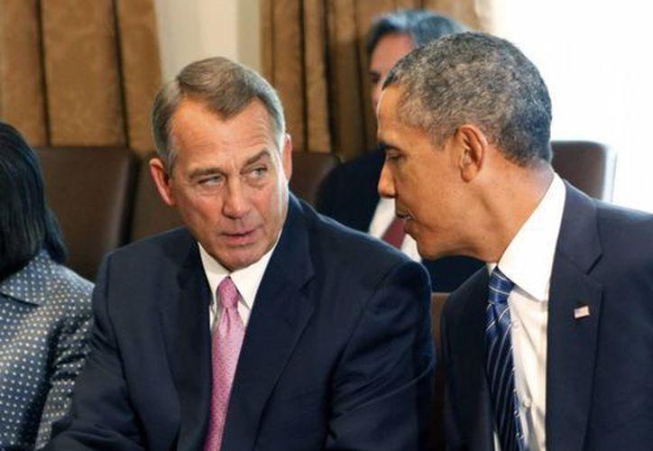 John Boehner atiende al presidente de Estados Unidos, Barack Obama, en la Casa Blanca. (EFE)