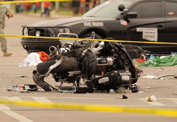 Una motocicleta de la Policía de Oklahoma yace en el piso, destruida, luego de que un vehículo arrollara a una parte del contingente de un desfile, en la Universidad local. (AP)