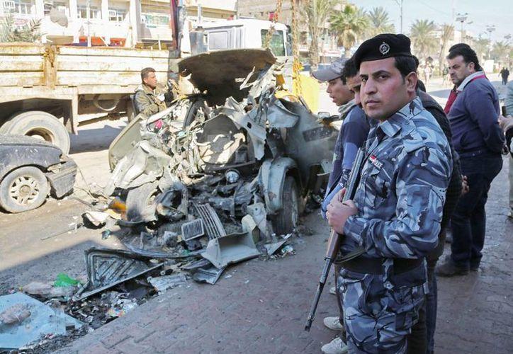 Policías en el lugar en que fue perpetrado un atentado con un auto bomba en el barrio de Shaab, en Bagdad, Irak.(Agencias)