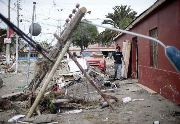 Un hombre camina entre escombros ocasionados por el tsunami posterior al terremoto 8.4 de magnitud sufrió Chile en días pasado. (EFE)