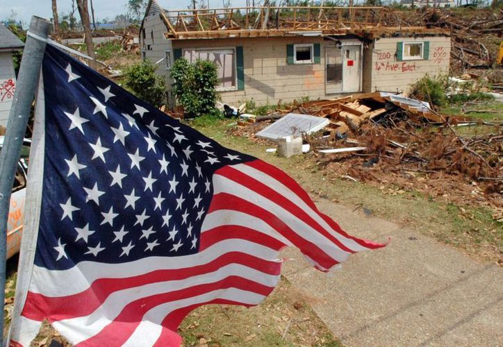 Una bandera ondea sobre los restos de un barrio asolado por un tornado en Tuscaloosa, Alabama. (Agencias)