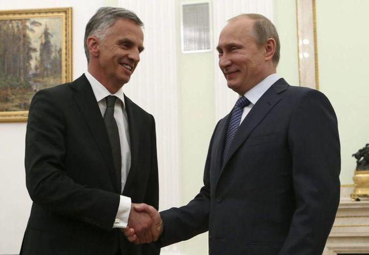 Putin (d), estrecha la mano del presidente de la Organización para la Seguridad y la Cooperación en Europa (OSCE), Didier Burkhalter, durante un encuentro en el Kremlin de Moscú. (EFE)