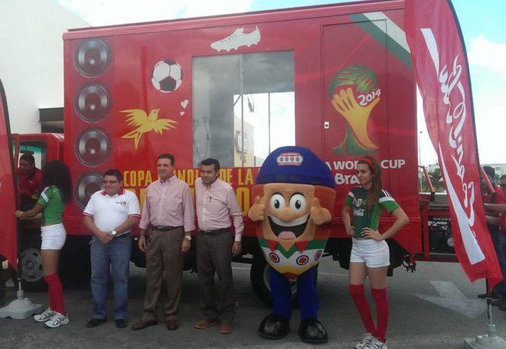 """Rafael Vázquez y Gimel Soberanis (al centro), en la puesta en marcha del """"Camión del Optimismo"""" de Coca Cola. (Milenio Novedades)"""