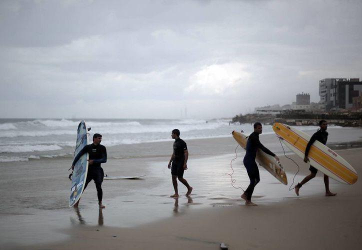 En total, son apenas dos docenas de surfistas que desafían las frías aguas para montar las olas del Mar Mediterraneo. (Foto: AP)