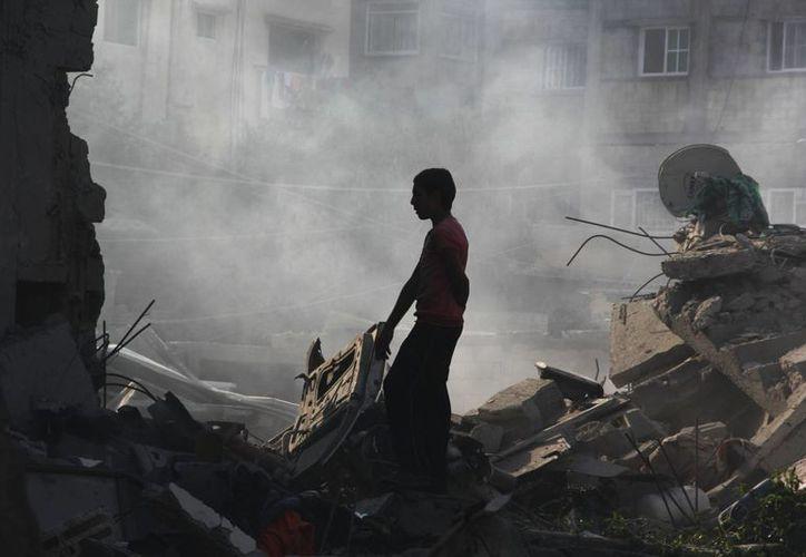 escombros de un edificio algunas pertenencias que aún sirvan, en Rafah, sureste de la Franja de Gaza, donde hoy se acordó ampliar 5 días el alto al fuego entre Israel y Hamás. (Foto: AP)