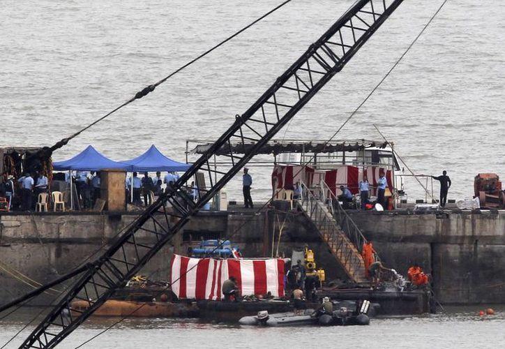 Buzos de la marina rodean el submarino de fabricación rusa INS Sindhurakshak, cubierto con una manta roja y blanca, en el astillero naval en Mumbai. (Agencias)