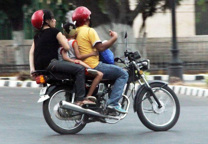 No basta cubrirse la cabeza, se deben portar cascos de motociclistas. Imagen de una familia a bordo de un vehículo de dos ruedas. (Milenio Novedades)