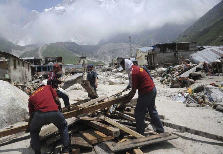 Trabajadores de los cuerpos de rescate preparando una hoguera para efectuar cremaciones en la India. (EFE)