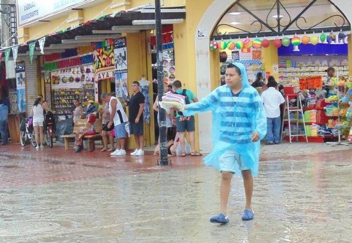 """""""¡Ponchos, ponchos, ponchos!"""", ofrecían en repetidas ocasiones a los turistas que se trataban de cubrir de la torrencial lluvia. (Yesenia Barradas/SIPSE)"""