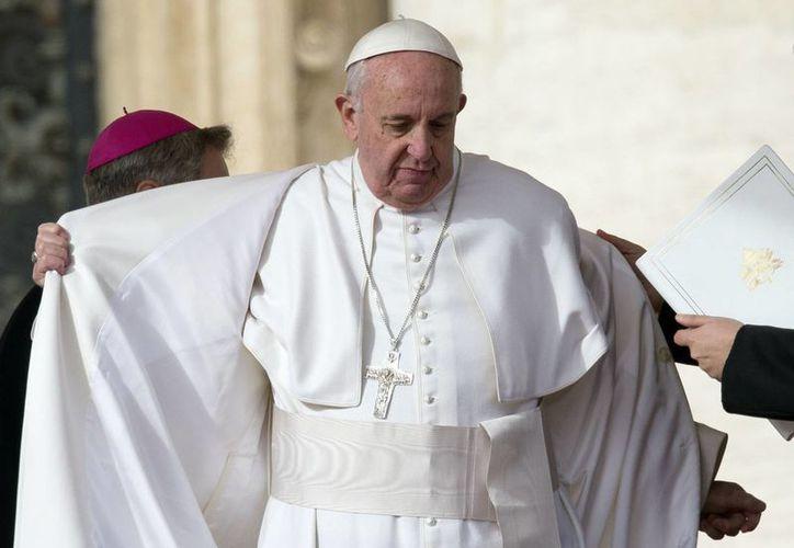 El Papa Francisco se quita su abrigo durante su audiencia general semanal en la Plaza de San Pedro, en el Vaticano. (Agencias)