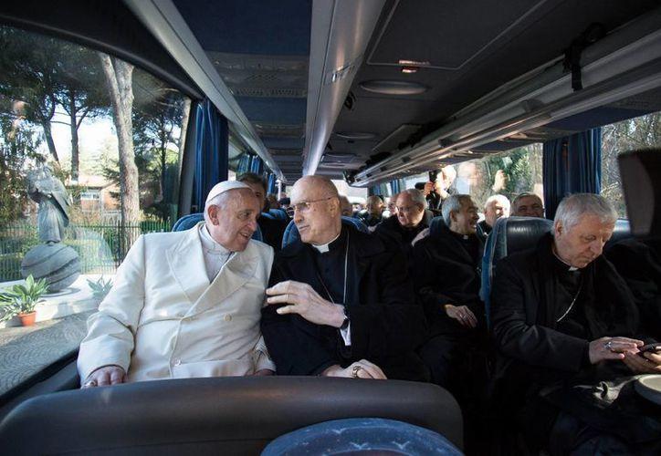 El Papa Francisco conversa con el cardenasl Tarciso Bertone durante el viaje en autobús que le llevó de regreso al Vaticano, tras finalizar su retiro en la localidad de Ariccia, con la Curia romana. (Foto: AP/L'Osservatore Romano)