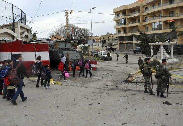 Un grupo de niños pasa por delante de la escena  de un atentado, en Beirut. (EFE/Archivo)