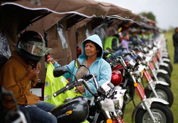 Una mujer entrega a su hijo un chaleco después de que entregó su caballo y carreta y recibió una motocicleta en Asunción, Paraguay, el viernes 21 de octubre de 2016. (AP Foto/Jorge Sáenz)