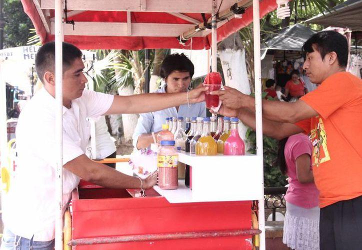 El calor del domingo familiar propició que tuvieran buenas ventas los oferentes de aguas de frutas, nieves y granizados. (SIPSE)