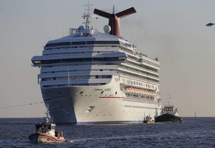 El navío está siendo llevado a puerto por tres remolcadores. (AP)