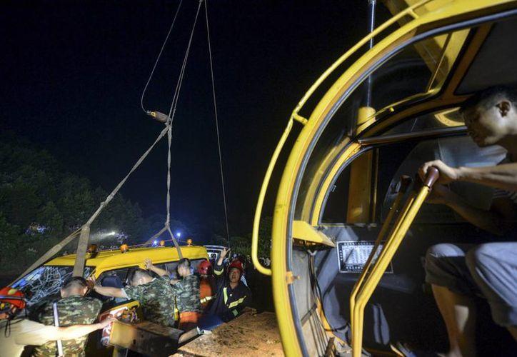 Imagen del momento en que los rescatistas sacan la minivan del estanque, la cual cayó con 8 niños y tres adultos, quienes fallecieron. (Agencias)