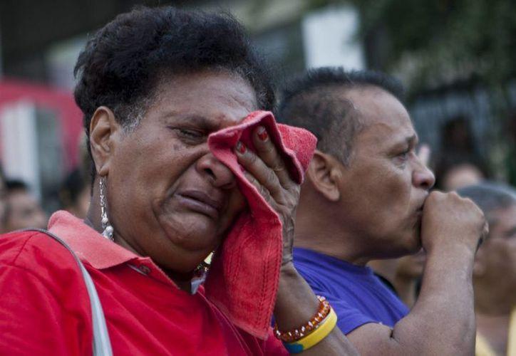 Venezolanos consternados por la muerte del mandatario, ocurrida hoy en Caracas. (EFE)