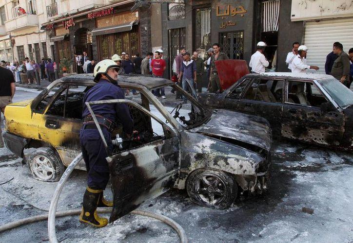 Bomberos apagan un incendio en un vehículos tras un bombazo en Damasco, Siria. (Agencias)
