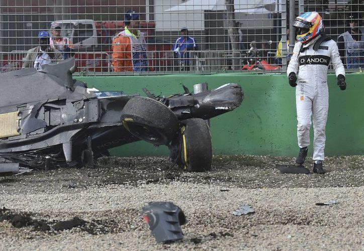Fernando Alonso observa el estado en que quedó su vehículo luego de sufrir un accidente, durante la carrrera del Gran Premio de Australia. (AP)