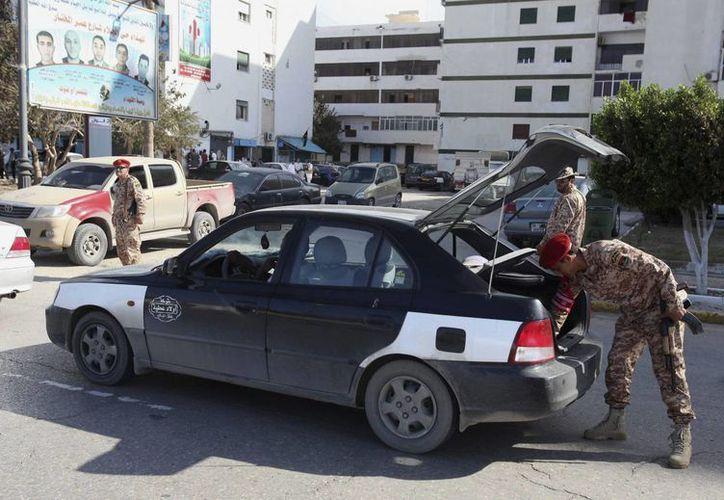 Un policía militar libio inspecciona un vehículo en un punto de control establecido en una calle de Trípoli. (EFE/Foto de contexto)