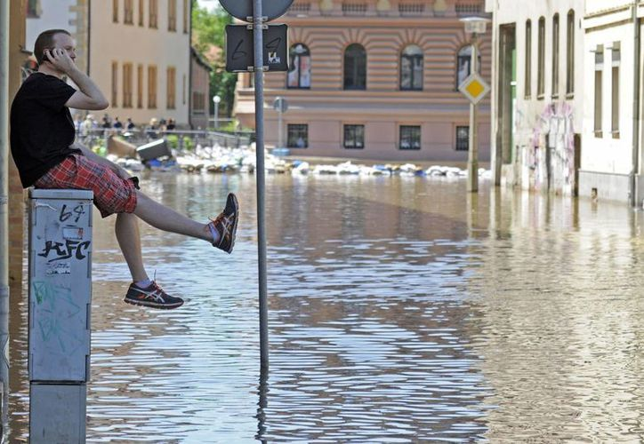 Un hombre habla por celular sentado en una estación de distribución de energía en un área inundada por el río Saale en Halle, Alemania. (Agencias)