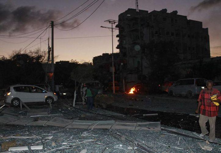 Varias personas transitan por el lugar de un atentado perpetrado en Mogasdiscio, Somalia. (EFE)