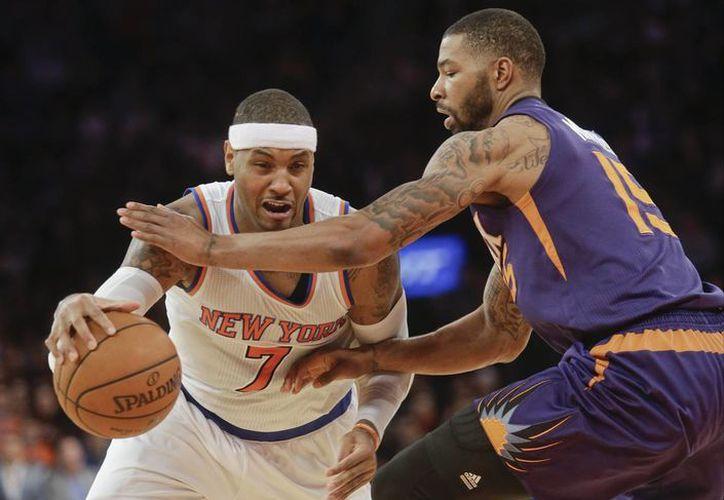 Carmelo Anthony (7), de Knicks, avanza pese a la marca de Marcus Morris (15), de Suns, durante la segunda mitad del juego entre ambas escuadras. (Foto: AP)