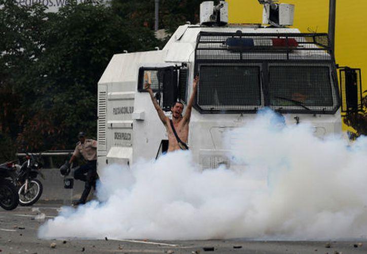 Un hombre desnudo se enfrentó a un camión militar ayer, durante las manifestaciones contra el gobierno venezolano. (Milenio)