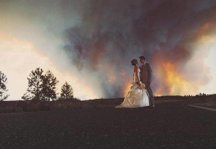 Los novios Michael Wolber y April Hartley posan para un retrato cerca de Bend, Oregon, con un incendio forestal como fondo el día de su boda. (Agencias)