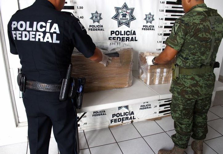 Imagen de un agente de la Policía federal y un elemento del Ejército al revisar los paquetes de droga decomisados en Correos de avenida Aviación. (Milenio Novedades)
