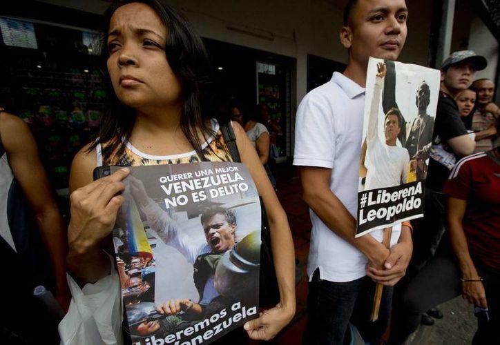 Seguidores de Leopoldo López se manifestaron con pancartas afuera del Palacio de Justicia, en Caracas, donde ayer comenzó el juicio al disidente. (Foto: AP)