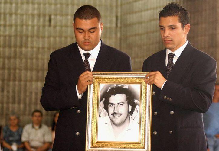 Dos jóvenes no identificados sostienen una fotografía de Pablo Escobar Gaviria durante una misa en su honor. (Archivo/EFE)