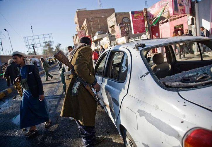 Un policía investiga uno de los vehículos dañados por una explosión, a las afueras de la academia de policía de Sana, Yemen. (AP)